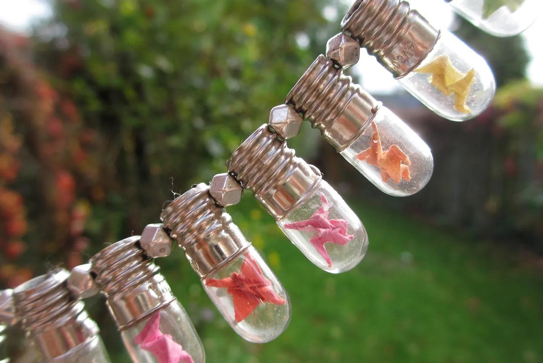 Mini origami cranes in mini light bulb necklace  Magical