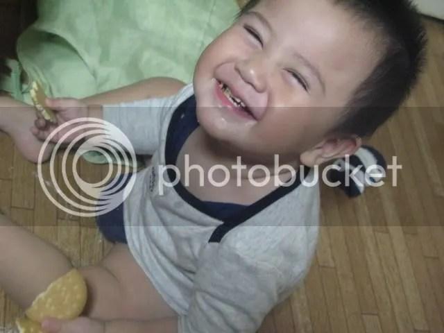 Kai menemukan biskuit dalam tas dan dengan mukanya yang suci (+nakal) , tersenyum begitu melihat aku mau foto.