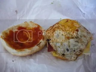 The top bun has a smear of ketchup. The burger is crowned with a fried egg.