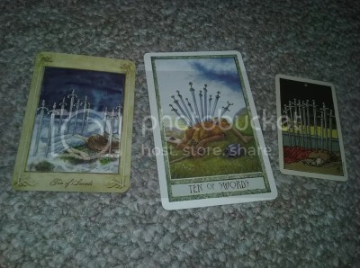 ten of swords, tarot cards by Llewellyn Tarot by Anne-Marie Ferguson, Druid Craft Tarot by Phillip Carr-Gomm and Stephanie Gomm, Smith-Waite Tarot copyright US Games; Photograph by author Juli D. Revezzo