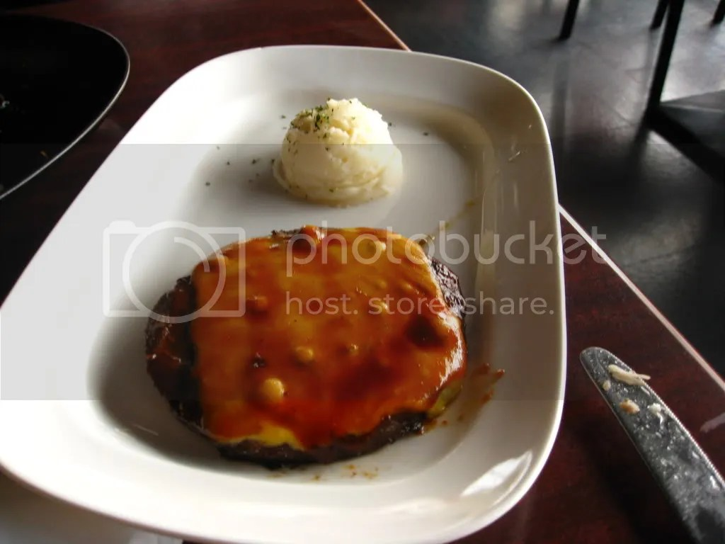 A really nice hamburger patty with some mash potato.