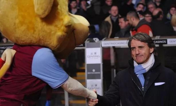 Manchester City manager Roberto Mancini shakes hands with Bella the Aston Villa mascot