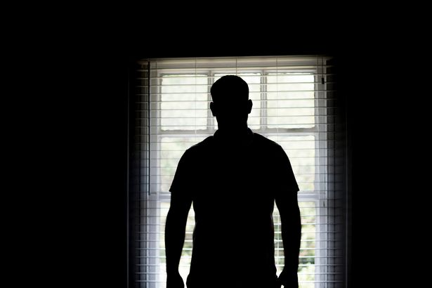 Silhouette of a man by a window.