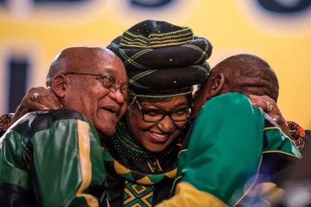 Winnie (centre) hugs former South African President Jacob Zuma (left) and then-Deputy President Cyril Ramaphosa