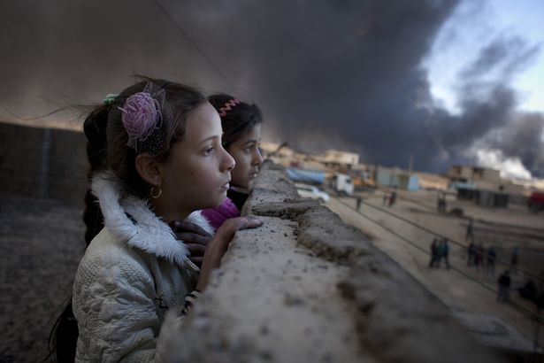 Two young girls look out at an oil well - one of many set alight by the Islamic State