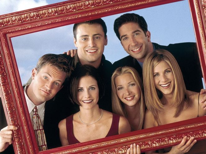 the cast of Friends looking and smiling through a picture frame