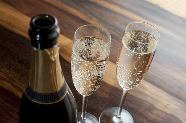 Two glasses filled with champagne next to a champagne bottle