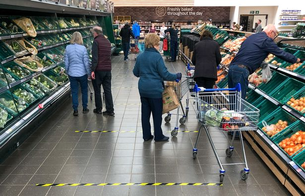 A ribbon marks 2 meter sections on the ground to implement social distancing measures in a Tesco store in Peterborough