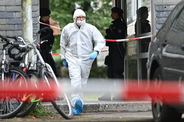 A forensic and police officers in front of an apartment building in Solingen