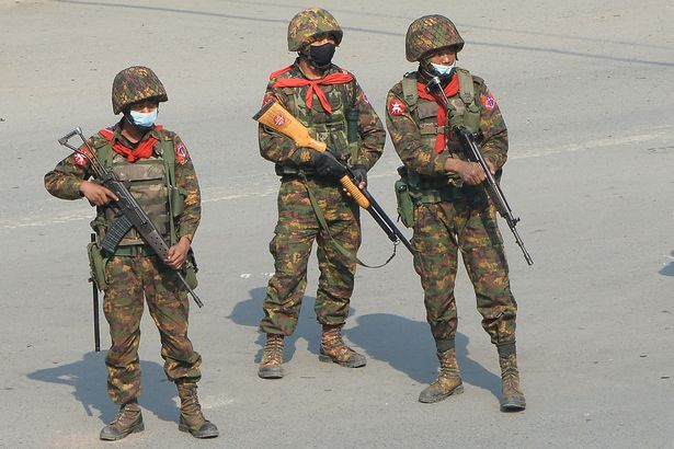 Soldiers carrying guns watch protesters stage protest against military coup