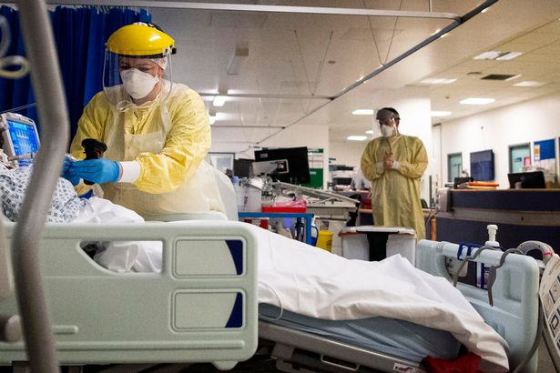 A nurse works on a patient in the ICU