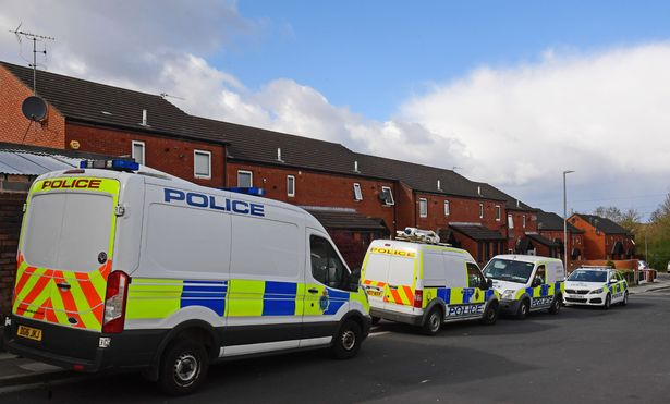 Police vehicles outside the house on Mersey Street, Parr, St Helens