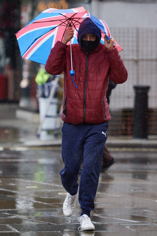 A man holds onto his Union flag umbrella as he walks