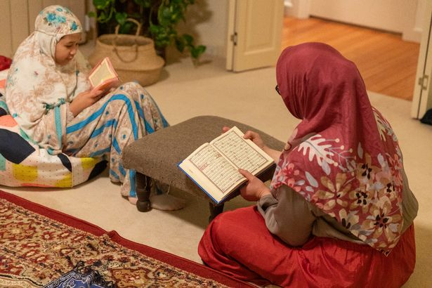 Dewi Andrina reads the Quran with her daughters following prayers on May 22, 2020 in Melbourne, Australia.