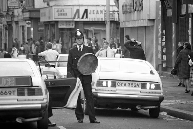 A police officer hopes to shied himself with a metal dust bin lid during Brixton riots