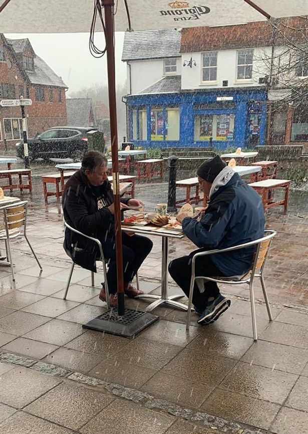 Two men eating their meal in wintry conditions as restrictions eased on Monday
