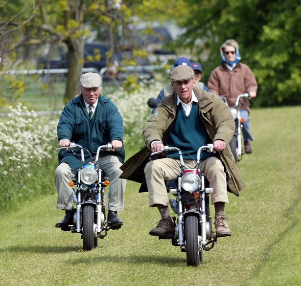 Prince Philip on small motor bike with Penny Romsey wearing headscarf and glasses