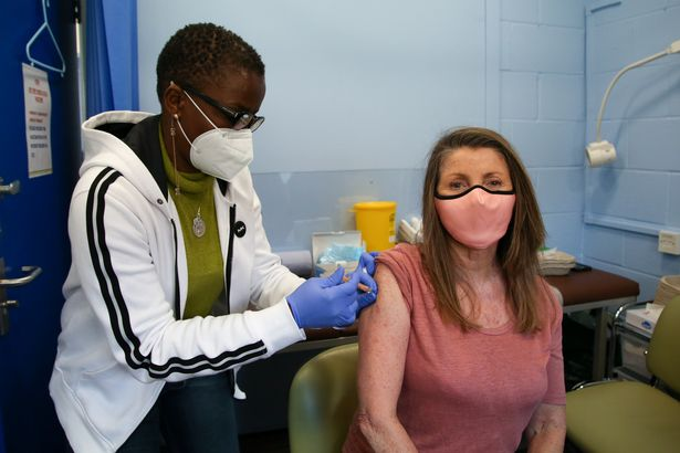 NHS staff member administers second dose of Oxford AstraZeneca Covid-19 vaccine to woman at vaccination center in Haringey, north London