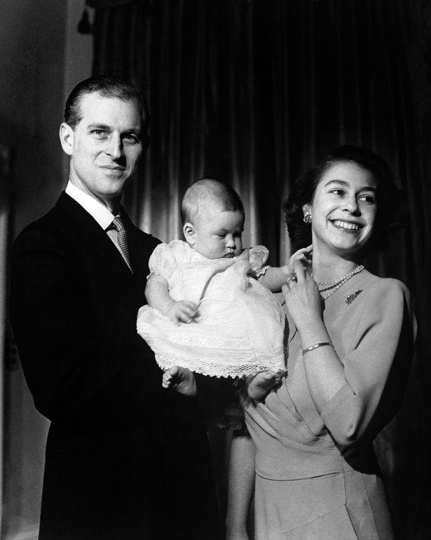 Queen Elizabeth II and the Duke of Edinburgh holding their first child Prince Charles