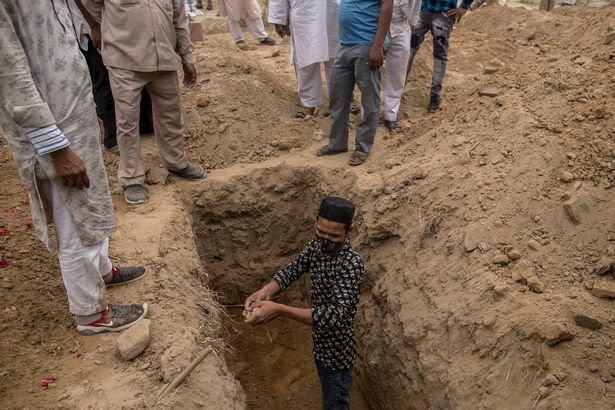 Family members and relatives prepare to bury a body of a patient who died of the Covid-19 coronavirus disease at a graveyard on April 20, 2021 in New Delhi,
