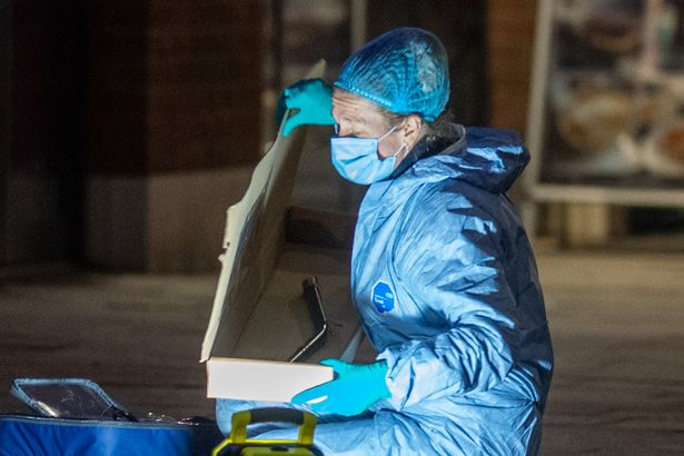 A forensic investigator recovers a metal pole on Barking Road in Canning Town following the fatal stabbing of a 14-year-old boy