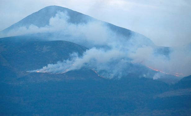 Clouds of smoke continue to rise from the mountain peaks near Newcastle, Northern Ireland