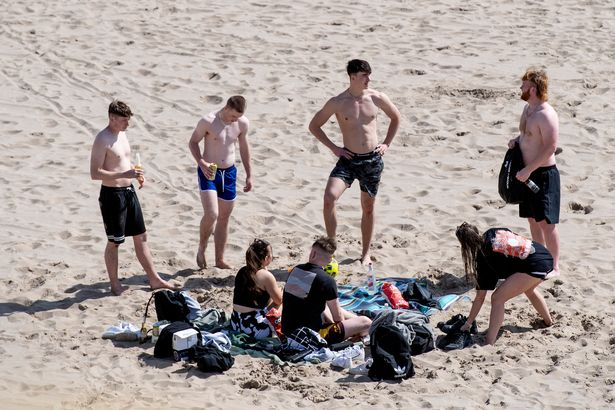 Friends enjoy the good weather at Barry Island in Cardiff, Wales