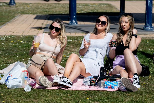 Three women enjoy a picnic in the sun in Barry, Cardiff