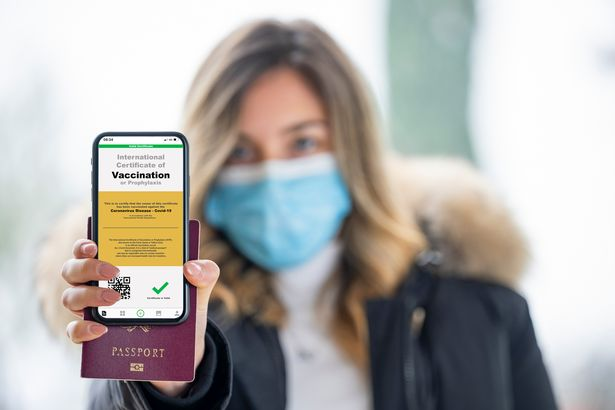 A defocused young girl, wearing a face mask, is holding a passport and a smart phone with a with an example of a certificate of vaccination against the Covid-19 disease