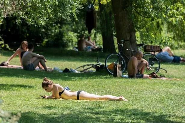 A woman sunbathing at Hampstead Heath Ponds London