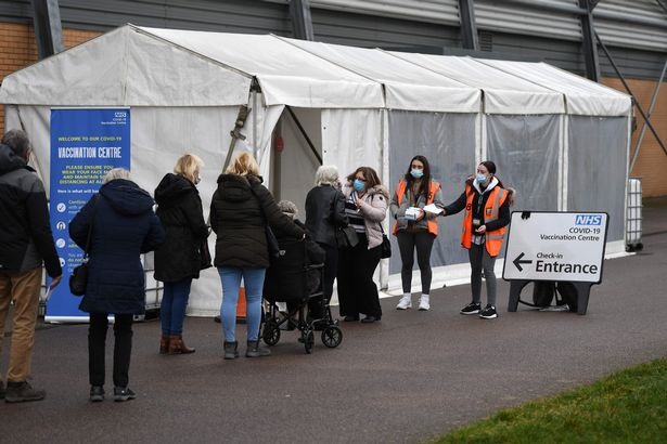 Members of the public wait in a queue to receive a dose of a Covid-19 vaccine at a temporary coronavirus vaccination hub set up at the Colchester Community Stadium in Colchester, Essex