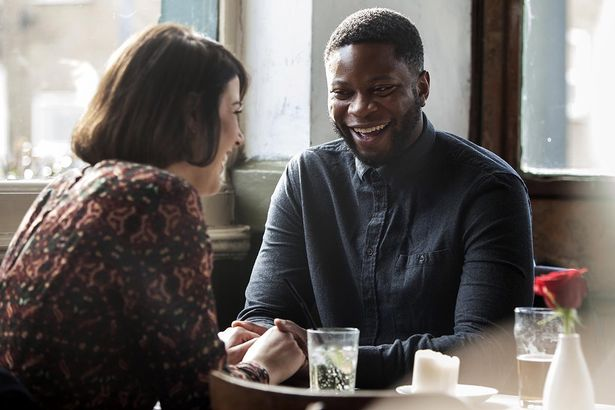 A couple together in a pub sitting at a table holding hand, while smiling at each other