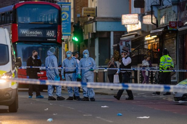 Forensic investigators on High Road in Willesden following the fatal stabbing of a 40-year-old man