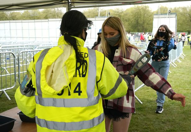 Concertgoers are checked through security as they enjoy a non-socially distanced outdoor live music event at Sefton Park