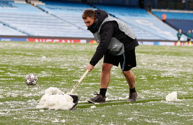 Snow is cleared from the pitch before the Manchester City v Paris St Germain match