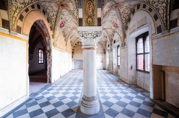 A hallway with mosaic ceilings and tiled floor