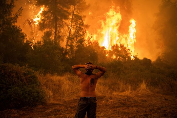 A local resident reacts as he observes a large blaze
