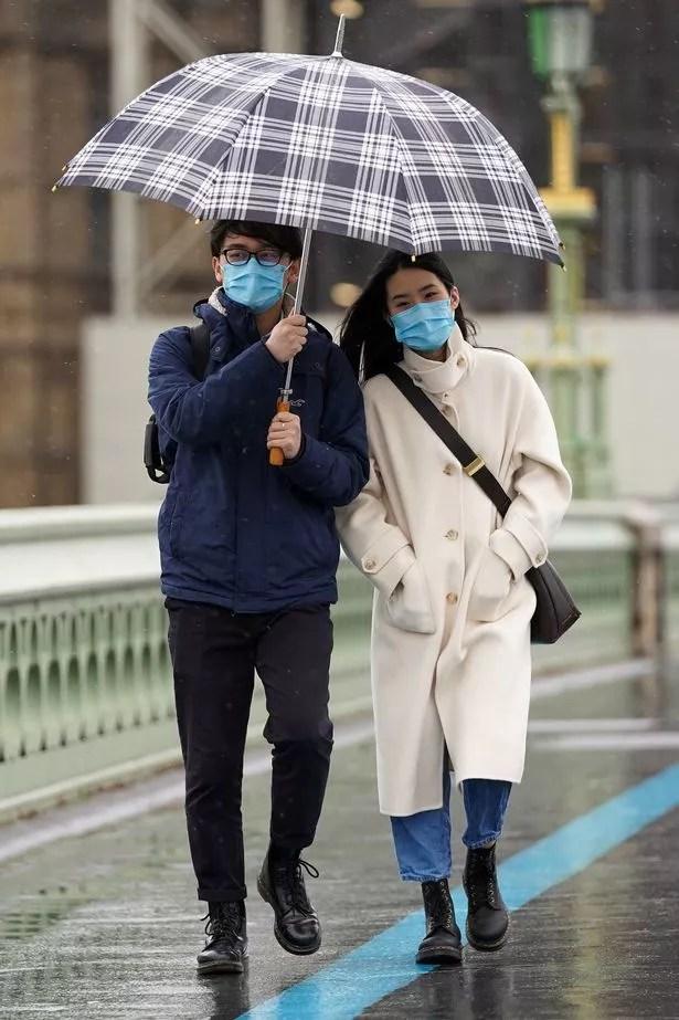 People walk across Westminster Bridge in the rain in London last weekend