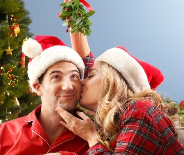 A Young Woman Kissing Her Husbands Cheek While Holding Mistletoe Over His Head While Sitting On