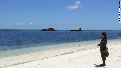 In this photograph taken in June 2014 a military personnel stands on the beach at Thitu island (Pag-asa) which hosts a small Filipino town as well as an airstrip used for civilian and military flights in the disputed Spratly islands in the South China sea. The Philippines said June 19, 2014 it would ask a UN tribunal to speed up its appeal to declare China's expansive claims to the South China Sea invalid. President Benigno Aquino's spokesman Herminio Coloma also confirmed that the Philippines would repair an airstrip on Thitu island, one of the disputed Spratly islands occupied by Philippine troops in the South China Sea. AFP PHOTO (Photo credit should read STR/AFP/Getty Images)