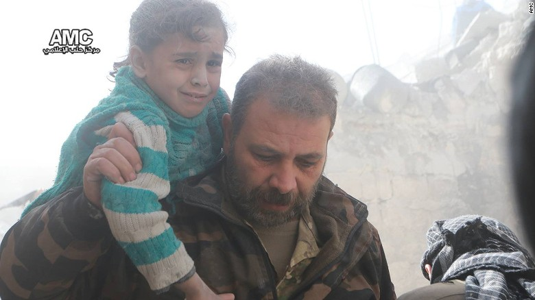 A man carries a child to safety in the wake of the Syrian regime's renewed airstrikes on Aleppo.