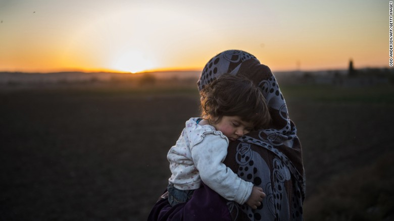 An Iraqi woman holds her child after crossing the Tigris River on Saturday, November 19, in the village of Tall Adh-Dhahab. Civilians are fleeing Mosul after an Iraqi-led offensive began in October to reclaim Iraq's second-largest city and the last major stronghold for ISIS in the country.