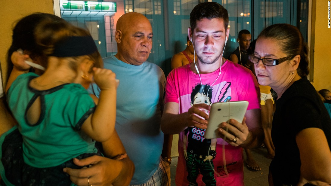 Raul Rossell, center, stands with son Aniel and other family members outside a Havana hotel.