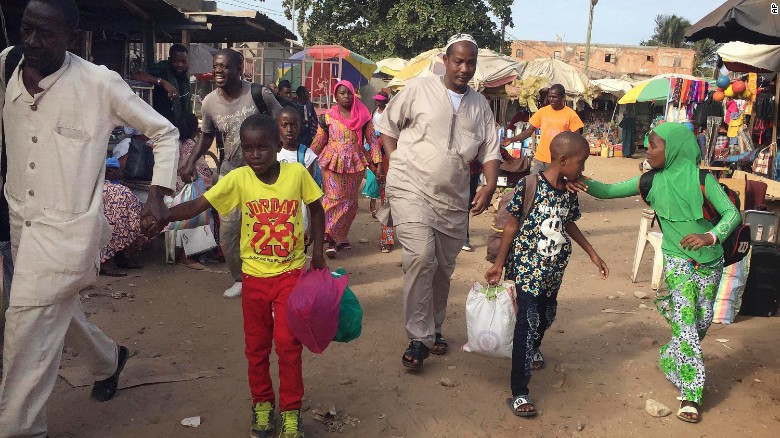 Facing uncertainty at home, people in Banjul, Gambia, head to a ferry this week bound for Senegal.
