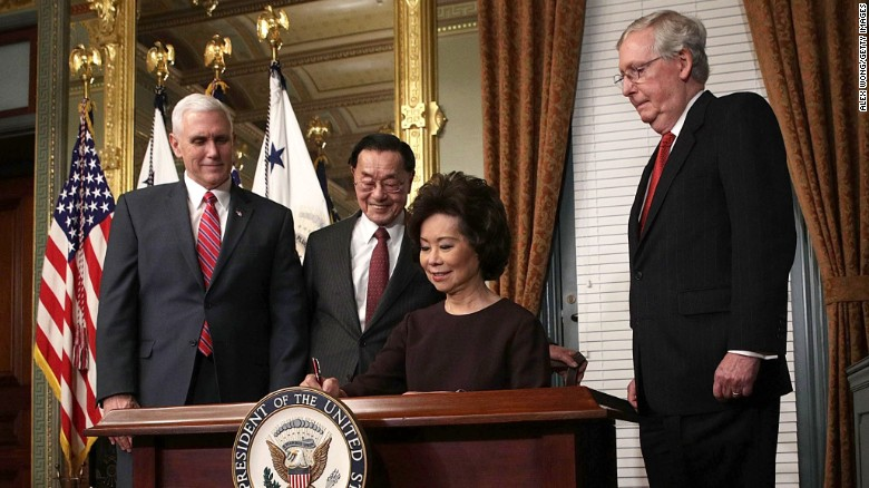 Elaine Chao, President Donald Trump's pick for transportation secretary, signs the affidavit of appointment during her swearing-in ceremony in Washington on Tuesday, January 31. Chao is joined, from left, by Vice President Mike Pence; her father, James Chao; and her husband, Senate Majority Leader Mitch McConnell.