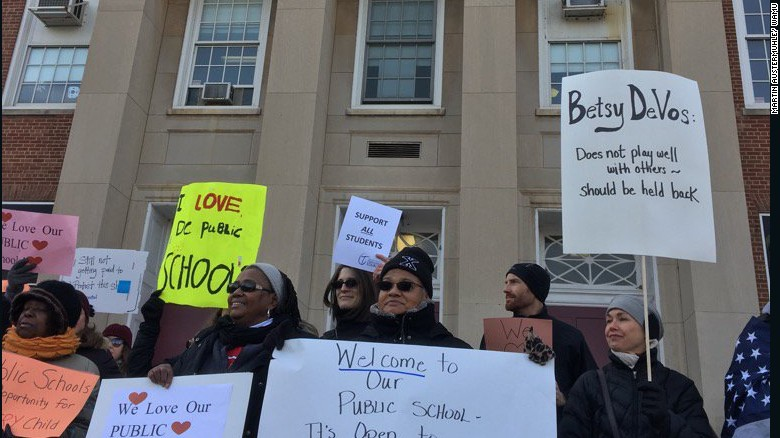 Protesters gather outside Jefferson Middle School Academy in Washington to oppose a visit by Secretary of Education Betsy DeVos.