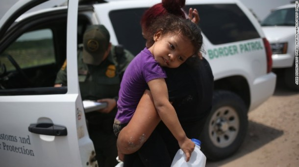 A mother and her 3-year-old child from El Salvador await transport to an immigrant processing center after they crossed the Rio Grande into the US on July 24, 2014.