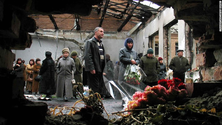 Friends and relatives of those killed hold a minute of silence in the wreckage of the school hall to commemorate the six-month anniversary of the Beslan attack.