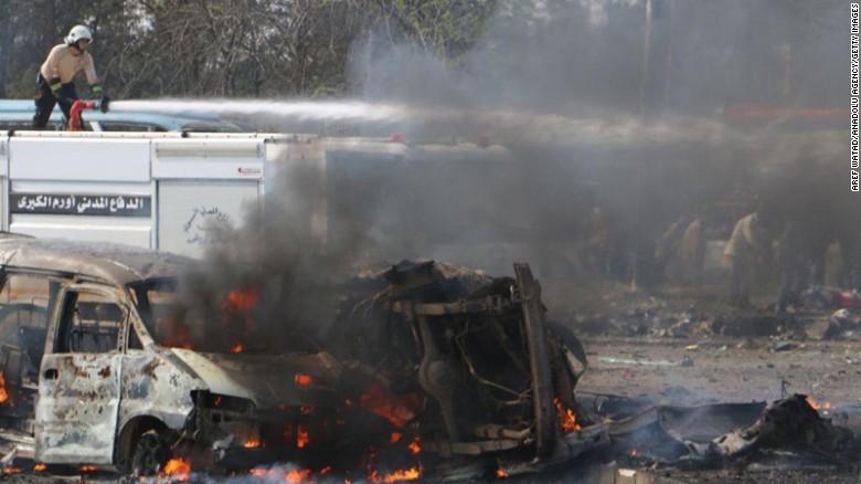 Civil team members try to extinguish the blaze Saturday near Aleppo.