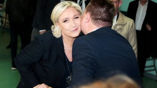 French presidential candidate Marine Le Pen kisses an electoral official after voting in Henin-Beaumont, northwestern France.